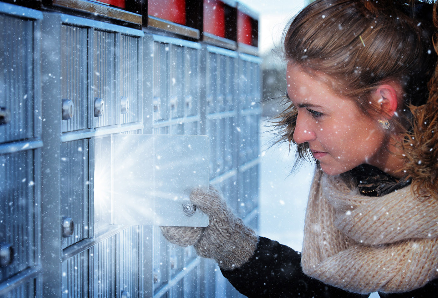 Pretty Woman Looking at Highlighted Mailbox in Winter - Stock Photo
