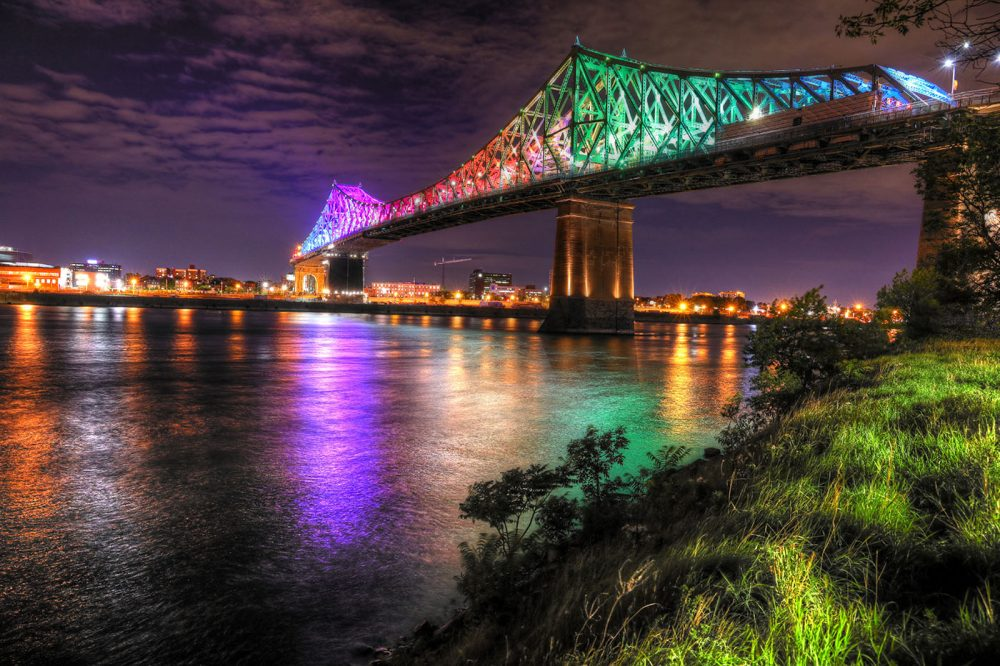Colorful Jacques Cartier Bridge in Montreal City during Covid 19 - Stock Photo